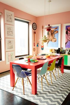 Peach dining room with chevron rug and colorful Eames chairs