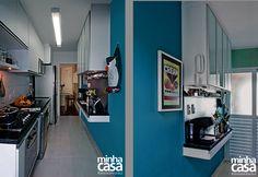 """A forma mais usual de superar a falta de espaço em cozinhas alongadas é alinhar o trio geladeira, pia e fogão em uma parede, cercando-o de armários. Neste projeto, a arquiteta paulistana Marina Moussi ainda conseguiu espaço, do lado oposto do cômodo, para uma leva de módulos aéreos e uma bancada: """"Desenhei esses elementos com profundidade de 30 cm, deixando 73 cm livres para circulação""""."""