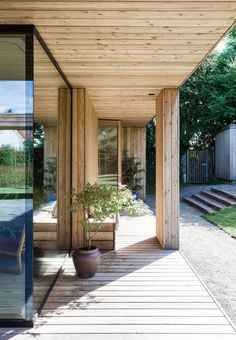 Covered wooden terrace with wooden bench and simple outdoor plants.