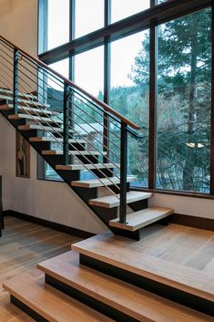 These large windows run from floor-to-ceiling to showcase stunning views and add a modern design element. Staircase Design Modern, Stair Railing Design, Home Stairs Design, Interior Stairs, Dream Home Design, Modern Design, Stairs Window, Open Stairs, House Stairs