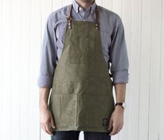 Maker's Apron Constructed from water resistant re-purposed military tent canvas, this handmade work apron is outfitted with bib and dual waist pockets as well as adjustable leather straps and brass rivets.