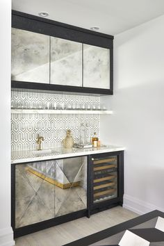 Chic contemporary black and white wet bar is fitted with antiqued mirrored cabinets positioned beside a glass front mini wine cooler and beneath a white marble countertop finished with a small sink with a brushed gold faucet. Muebles Living, Home Bar Designs, Wet Bar Designs, Mini Bars, Small Sink, Built In Bar, Mirror Cabinets, Dark Cabinets, French Country Kitchens