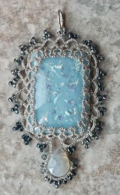 "Blue Ice        Another Tatsmithed pendent made from a focal bead and two strands of metallic sewing thread.  The pendent is 1.5"" across and 3"" tall."