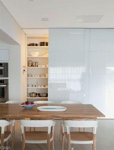 Um painel de azulejos coloridos se destaca nesta cozinha repleta de materiais clarinhos, como o Corian das bancadas (Studio Vitty), o vidro dos armários (Cinex) e o porcelanato areia Ilva (Portoro). O louceiro é fechado por três folhas de correr com vidro branco (Cinex). Projeto da arquiteta Consuelo Jorge. @conjorge #cozinha #kitchen #dining