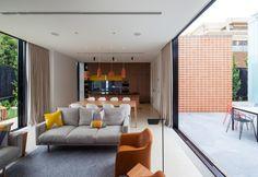 Il volume moderno si sviluppa su un solo livello e ospita una zona giorno ariosa, con due lati vetrati. Da una parte affaccia sulla corte centrale e dall'altro lato guarda al giardino di casa