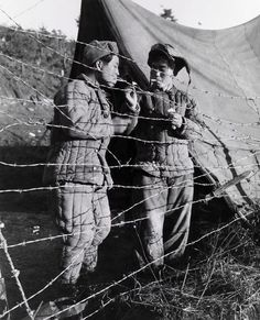 Korean prisoners of war smoke cigarettes near the edge of a compound. Photograph by Robert H. Mosier, U.S. Marine Corps.
