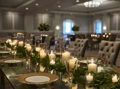 To create a romantic and refined tablescape for a wedding in the Ballroom at The Ritz-Carlton, Half Moon Bay, designers adorned the center of tables with garlands of rose leaves and candles of various shapes and heights.