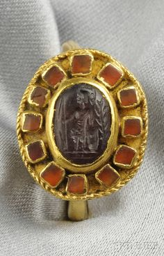 Ancient Jewelry // Ancient Roman Gold and Garnet Intaglio Ring, the garnet intaglio depicting a soldier, framed by bezel-set orange glass Roman Jewelry, Jewelry Art, Jewelry Gifts, Jewelery, Jewelry Design, Fashion Jewelry, Gold Jewelry, Jewelry Shop, Fine Jewelry