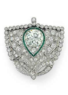An Art Deco diamond and emerald brooch, circa 1925.  Designed as an old-cut diamond shield-shaped plaque trimmed with a collet-set old-cut diamond border, centring upon a cluster of old-cut diamonds with calibré-cut emerald pear-shaped surround, mounted in platinum and white gold. #ArtDeco #brooch