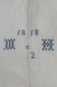 Homespun linen sheet, c.1818. Oatmeal colored linen is hand-embroidered in blue cross stitch with initials MH.