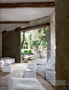 White cushioned floor seating with a sliding wood door leading out to the patio