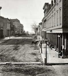 "1864. ""Atlanta, Georgia. Street view."" To the right, a hatter. Everywhere else, dirt and mud. Wet plate glass negative by George N. Barnard"