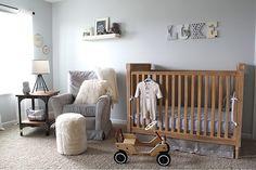 Quarto de bebê cinza e azul com berço madeira.