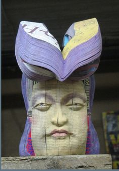 Long-Bin Chen carves Budda heads out of old phone books creating budda heads filled with hundreds of names.  Love this!