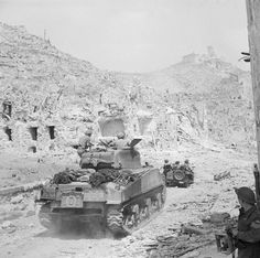 BATTLES MONTE CASSINO JANUARY - MAY 1944 (NA 15079)   A Sherman tank and jeep of the 4th Brigade entering the ruins of Cassino. The monastery of Cassino had formed the focal point of the German Gustav Line which they had successfully defended since November 1943. The fourth offensive led by Polish and British troops secured Cassino for the Allies and caused the Germans to retreat north of Rome, which was then declared an 'open city'.