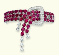 A RUBY AND DIAMOND BRACELET Of garter design, composed of three rows of oval-shaped rubies to the drop-shaped diamond fringe terminal and pavé-set diamond buckle clasp, 18.5 - 16.0 cm long
