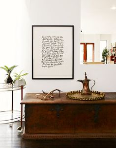 White walls, brown coffee table, gold accents, and black and white worded wall art