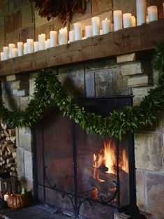 Fireplace mantle adorned with candles. Holiday decor inspiration.