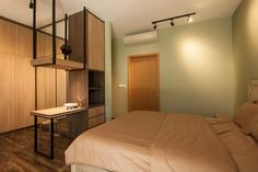 A dressing table serves as a divider between the bed and the walk-in wardrobe in this bedroom.