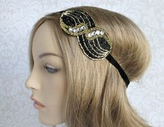 This art deco headband is made up of black and gold seed beads along with eight rhinestones for added glitz. This piece is great for a night on