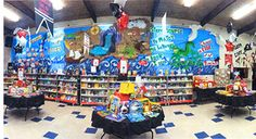 """Our Fall 2013 National Contest winner on the Elementary level is St. Timothy's Lutheran School in San Jose, who stole our hearts with their theme """"Every Book is a Treasure!""""  The main hall of the building was transferred into a Pirates Adventure, including a pirate ship, with dock, crow's nest, parrots, and a full sail. The scene was embellished with pirates, piles of gold coins, an oasis with palm tree, and a treasure chest guarded by a very large crocodile!"""
