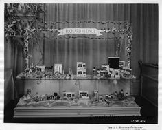Richard Hudnut products including whirl-a-wave curlers, home permanent, nail polish, shampoos and cream rinses. The display is ornamented with flowers, and netting.