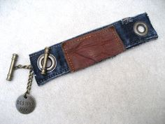 Authentic Levi upcycled bracelet. This Levi denim cuff is made with antiqued brass grommets and held together with an antiqued brass chain and toggle, cuff link style. Approximately one inch of chain shows, giving this bracelet its unique look. From the chain dangles a brass charm with the word DESTINY. The grommets are applied with a press machine. The toggles have a small peace sign engraved on the ends, a fun detail of this piece.    THIS LISTING IS FOR 1 BRACELET, THE EXACT ONE IN THE…
