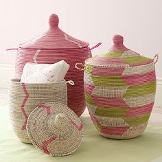 """Senegalese Storage baskets from Serena & Lily  - Pink, Set of Three $290.00    Hand made in Senegal from natural fiber and recycled plastic. (Also in Blue or Navy/Green.) Colors, patterns and sizes will vary slightly from item pictured, as each unit is constructed by hand using reclaimed plastic material. Set of three baskets. Small: 15"""" DIAM x 19"""" H. Medium: 18"""" DIAM x 26"""" H. Large: 22"""" DIAM x 30"""" H. (Item # 3BXT-01)"""