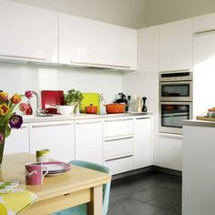 To make a white kitchen design work team polished slate flooring and a shiny glass splashback with white gloss units for a streamlined, easy-clean finish, then add colour with bright cookware.