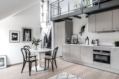 The metal staircase in this beautiful attic home gives this space a industrial loft look. A minimal grey kitchen is placed underneath the metal staircase, making space for a small living area and on t