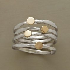 GOLD DISK RINGS--Four gently irregular sterling silver bands, each dotted with a spot of 14kt gold. Sundance exclusive set of 4 in whole sizes 5 to 9.