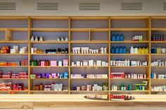 Noting that white, with its clinical connotations, was the usual choice for pharmacies, the design team chose colours that were warm and homely, but also related to good health. The space has birch-topped plywood cabinetry with rose pink and brass details, and an illuminated green cross by Eindhoven studio V3RS sits in one corner.