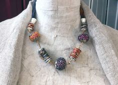 This beautifully textured, one of a kind, colorful fabric necklace features hand-painted silk strands, 4 tube-shaped fabric beads, and three large beaded beads. Bead caps are used for each necklace element and provide a nice contrast to the fiber. A large branch-shaped toggle clasp completes the necklace. The colors are mauve/soft purple and terra cotta (see pictures). See the fourth image for additional product information, and the fifth image for a view of how the product will be packa...
