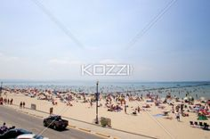 view of car on road with beach in background. - View of car on road with beach and clear sky in background.