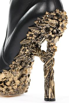 A pair of Alexander McQueen black leather thigh-high boots, 'Angels & Demons' collection, Autumn-Winter, 2010-11. labelled and size 38, with four straps and buckles at intervals, the upper leg of soft, crinkled leather, the heels and platform soles formed of gilt filigree resin moulded with bunches of blooms