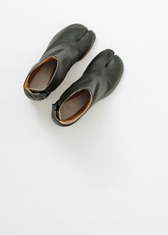 """Split toe leather ankle boot in dark green, inspired by a traditional Japanese design. Cylindrical 3.25"""" stacked wood heel with rubber plate and tan leather sole. Hidden silver hook closures at inner ankle. Single Maison Martin Margiela white stitch at back ankle. Dust covers included."""