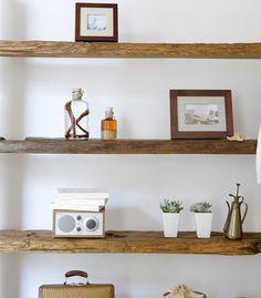 Prateleira feita com madeira de demolição. Vasos, porta-retratos e acessórios decorativos.