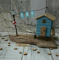 Salt Spray Handcrafted original artwork by DriftwoodSails 🌊 Here is your very own timber Beach Hut to own, with striped weatherboard in dusky blue, driftwood door & roof, lamppost, life belt, rope coil, bucket with fishing nets, LOVE flag bunting 💙 Perfect Mothers Day gift, housewarming gift for someone moving to a new home, a special birthday present or a unique 5th wedding anniversary gift (wood). This piece is set on a beautiful piece of weathered Kentish driftwood and has been lovin...