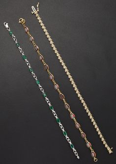 A lot of three bracelets, featuring diamonds, garnets, and emeralds set in gold.