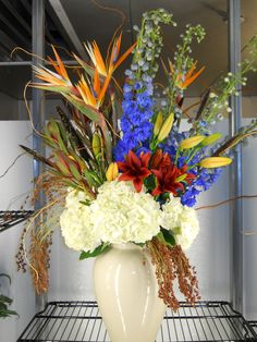 Modern Upscale Arrangement by Texas Blooms (birds of paradise, blue hybrid delphinium, rust orange lilies, white hydrangea, safari sunset, mixed foliage)
