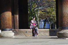 A young girl sits elegantly in traditional Japanese garments among the towering pillars of Nanzen-ji, a temple in eastern Kyoto, Japan.