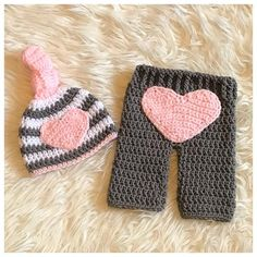 Crochet Heart Newborn Baby Outfit. Perfect little outfit for Valentine's Day! This sweet set is Size newborn. This set includes: - A white & gray striped knot hat trimmed in light pink with a light pink heart sewn onto the front of the hat. - A pair of gray pants with a large light #CrochetValentines