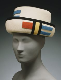Woman's Hat | Designed by Sally Victor, American, c. 1894-1977 | United States, circa 1962 | Materials: wool felt, grosgrain ribbon | Sally Victor frequently made references to works of art in her hats, including this example from about 1965. This hat in white wool felt appliqued with blue, orange, and black wool felt stripes, recalls the works of Piet Mondrian | Philadelphia Museum of Art