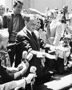 Frank Sinatra, surrounded by cameras, places his hands and feet in the cement at Grauman's Chinese Theater on July 20, 1965. Friend Dean Martin and daughters Tina and Nancy attended the ceremony with him.