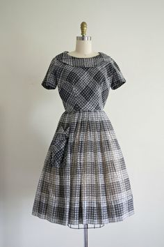 Very cute 1950s full skirt cotton day dress. Made from very lightweight grey checkered cotton. Big collar on the boat neckline. Nipped at waist. Lightly pleated very full skirt with big side pocket. Big decorative button closure in the back. This 50s pin up perfect Mad Men beauty would be perfect for the warm weather because the fabric feels very delicate and breathable. Fully lined. Photographed with the crinoline not included in the sale. Label: Manford  Fits like smaller medium. Please…