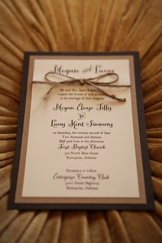 tan and brown are paired together for these rustic invitations with the added touch of a twine bow - thereddirtbride.com - see more of this wedding here