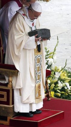 current Pope holding bones of first Pope, St Peter