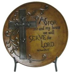 """Joshua 24:15 scripture is inscribed onto this As for Me and My House Charger with Metal Stand. The plate charger is formed from polyresin and embellished with a large cross and scroll details. A black metal stand is included with this decorative piece.    Dimensions:      Width: 18""""    Height: 18""""      Full Text: As for me and my house we will serve the Lord. -Joshua 24:15"""