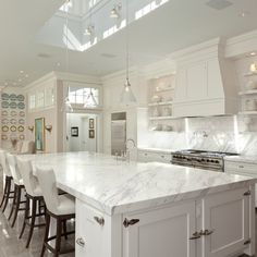 All white kitchen design with skylight setting the stage for crisp white cabinets paired with calcutta marble countertops, calcutta marble backsplash backsplash paired with subway tile backsplash. All White Kitchen, White Kitchen Cabinets, Kitchen Cabinet Design, New Kitchen, Kitchen Decor, Kitchen Ideas, Shaker Kitchen, Kitchen Cabinetry, Country Kitchen