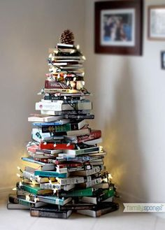 17 bookish Christmas decoration ideas for the home, including this tabletop book tree complete with string lights. Full of fun Christmas crafts!